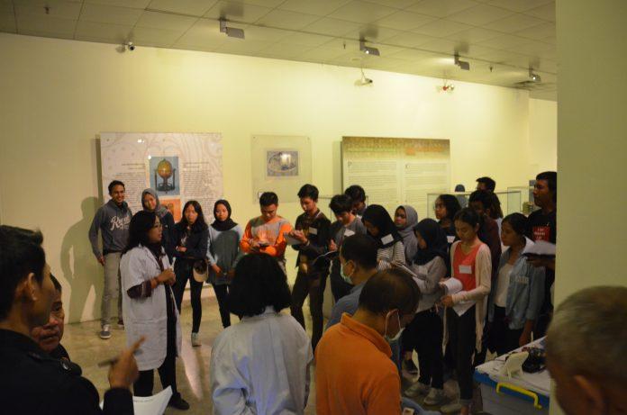 Mahasiswa Jurusan Arkeologi UI Mendengarkan penjelasan